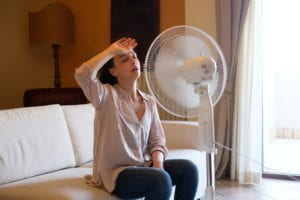 woman-looking-hot-in-house-and-trying-to-cool-off-with-fan